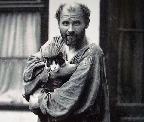 Fotografia d'epoca che ritrae Gustav Klimt con un gatto in braccio di fronte il suo atelier.